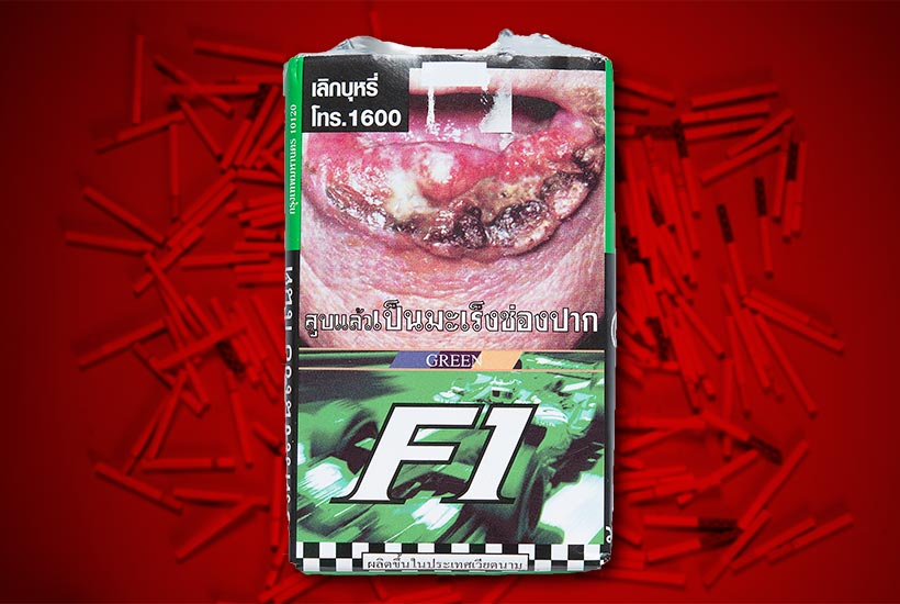 cigarette pack with racing car graphic and graphic warning of mouth cancer victim