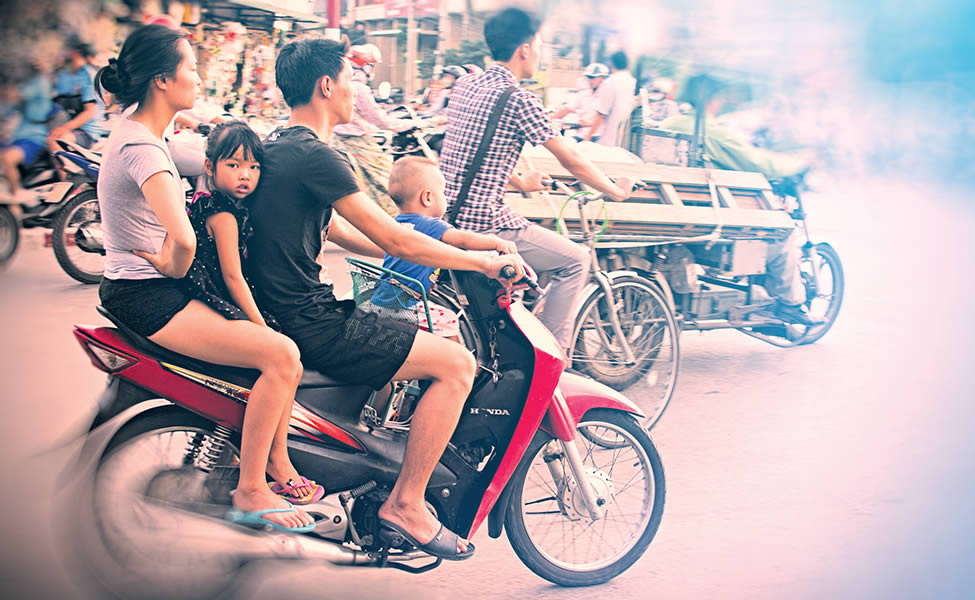 Protected? A family of four rides helmetless through Hanoi traffic.