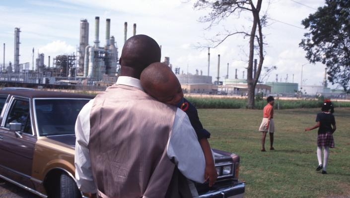 A family leaving church services surrounded by chemical plants