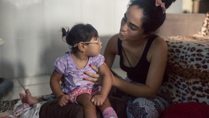 Dhulha Alen Silva do Nascimento and her daughter, Valentina, share a moment at home.