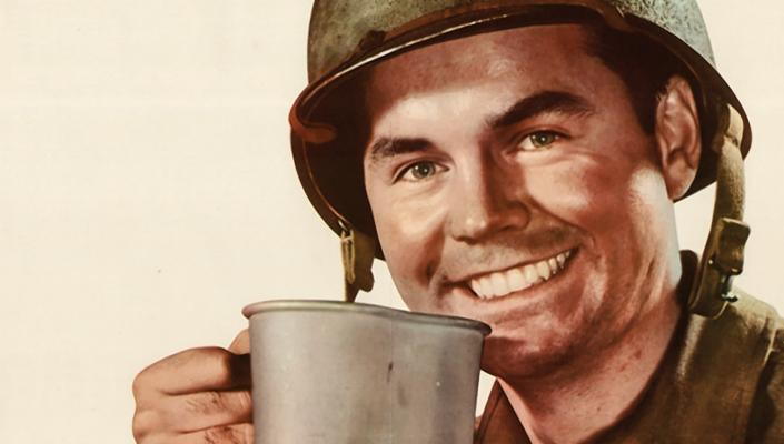 Smiling WWII GI drinking coffee