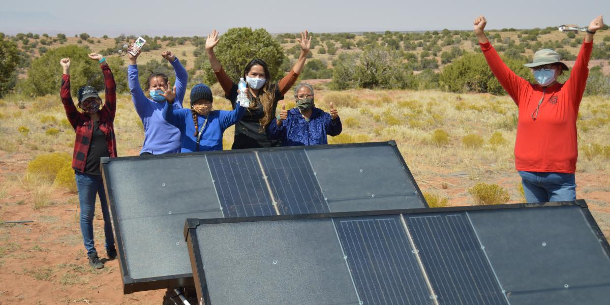 Navajo Nation residents cheer next to hydropanels