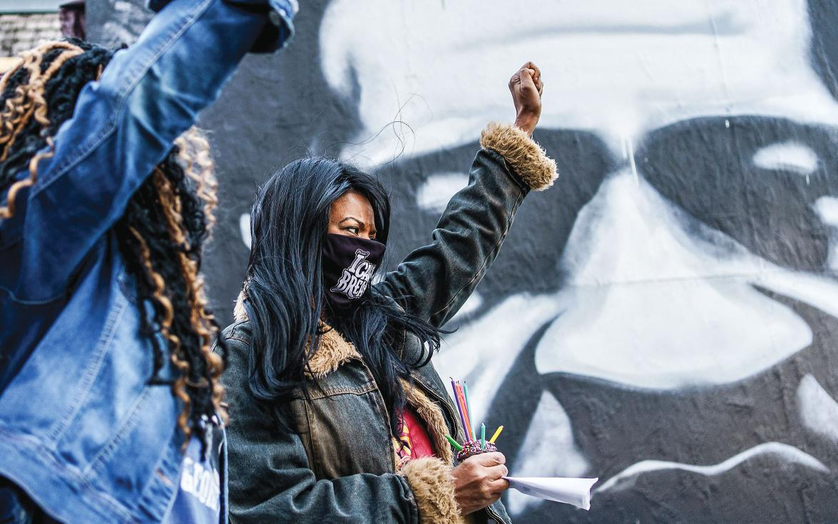 Black women in front of a George Floyd mural with raised fists.